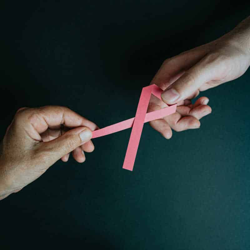 two hands connected by a breast cancer awareness ribbon to symbolize cause marketing