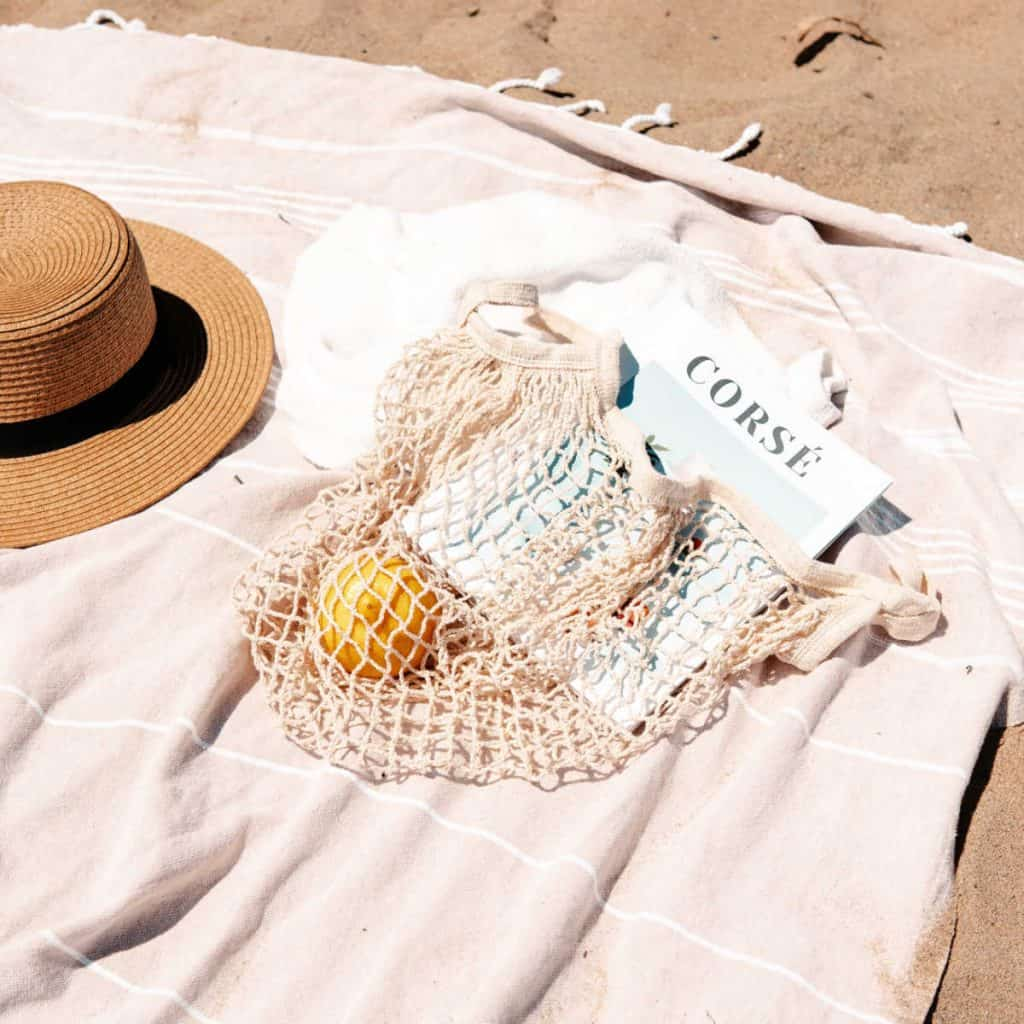 straw hat and magazine on the beach